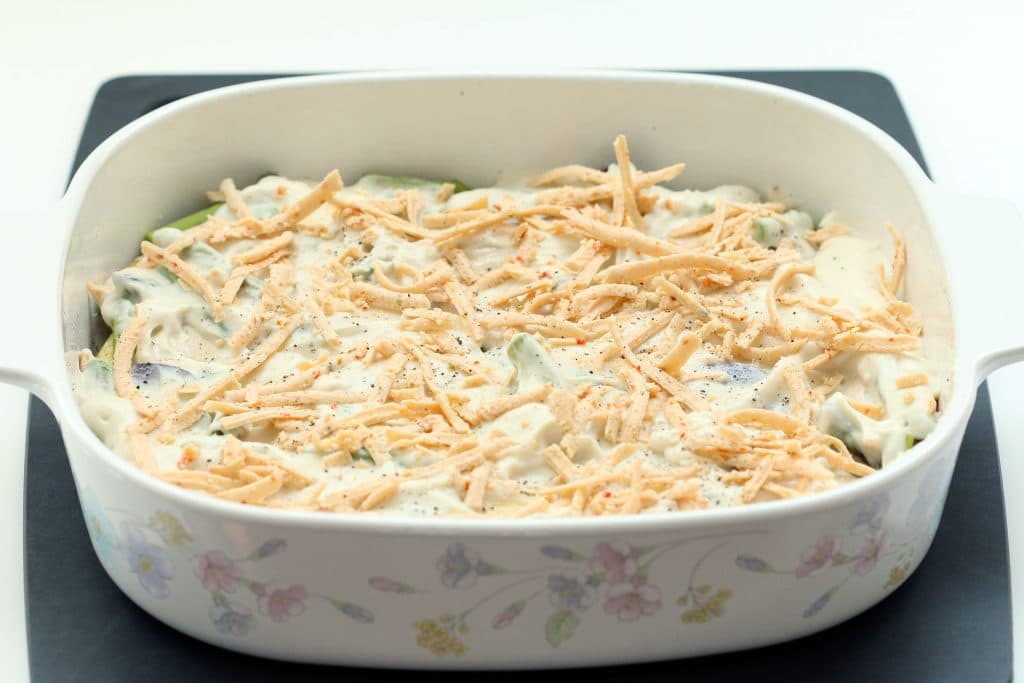Vegan Au Gratin Potatoes - Veggies in Baking Dish with Vegan Cream Sauce and Vegan Cheese